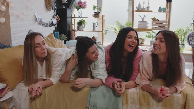 candid shot of four girlfriends having a laugh while hanging out during a slumber party - slumber party stock videos & royalty-free footage