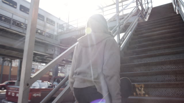 A candid, young, black woman entering a Brooklyn, NYC subway station with her skateboard - 4k