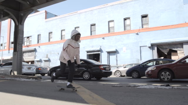 A candid young, black woman skateboards through the streets of Brooklyn, New York City.