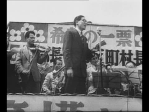 candidate speaks emphatically at outdoor campaign event in japan / montage elderly, middle aged people listen / montage orchestra on stage plays as... - 選挙点の映像素材/bロール