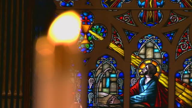 vídeos y material grabado en eventos de stock de candle burning near stained glass of jesus, rack focus - jesucristo