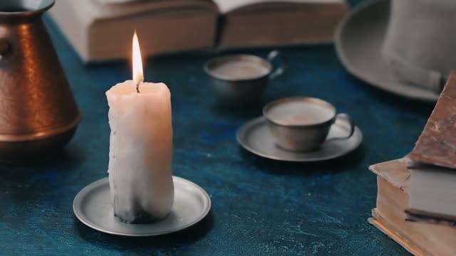 vídeos de stock, filmes e b-roll de vela queimando na mesa com café e livros - old book