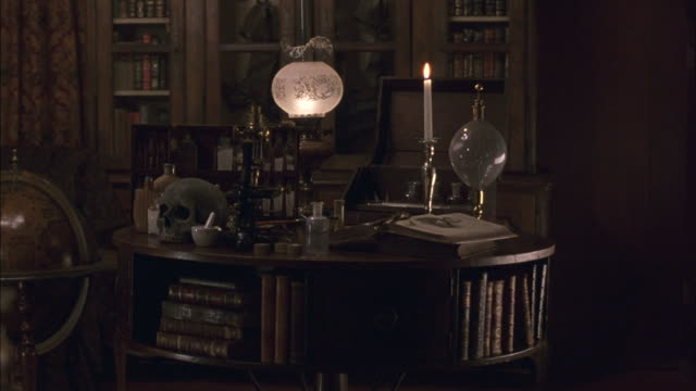 A candle burns in a small library.