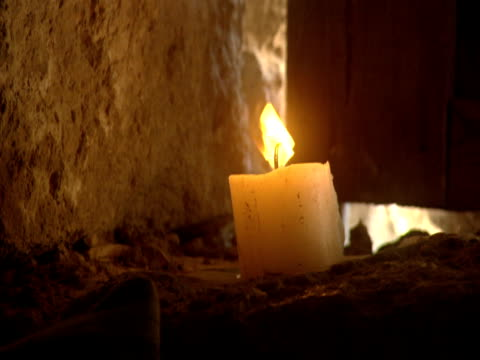 a candle burns in an earthen room. - candle stock videos and b-roll footage
