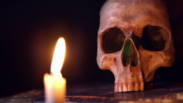 a candle flickering near a human skull is suddenly blown out. - candlelight stock videos & royalty-free footage