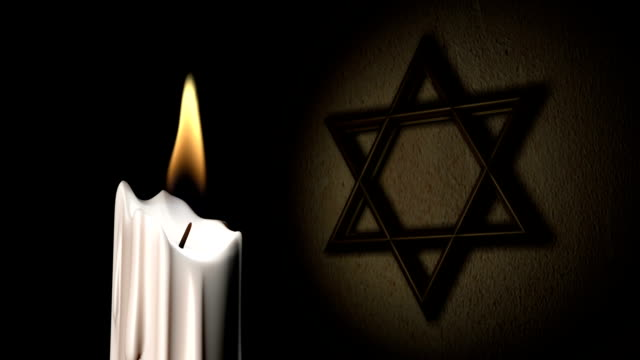 a candle flickers in front of a star of david. - star of david stock videos and b-roll footage