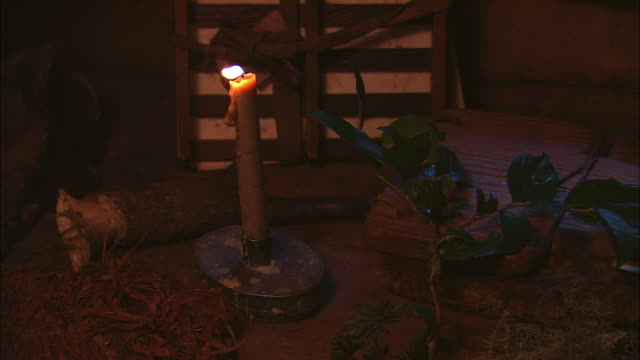 a candle flickers on a table near an open journal. - western script stock-videos und b-roll-filmmaterial