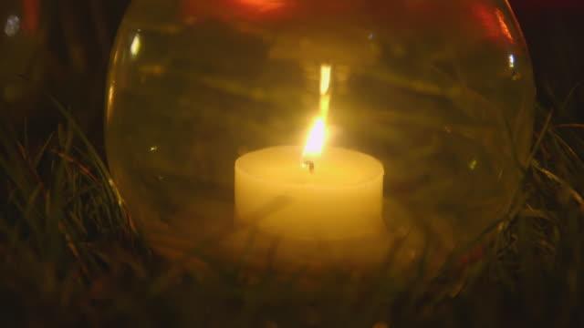 vídeos de stock, filmes e b-roll de candle in yellow glass holder on grass - festival tradicional