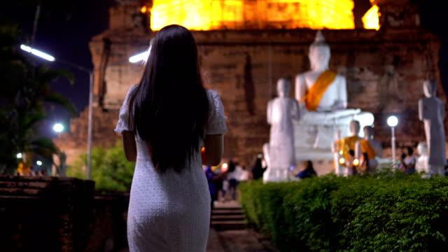 vidéos et rushes de lumière de bougie rougeoyant dans les mains de femme asiatique - une seule adolescente