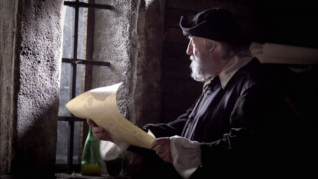 a candle snuffs out in a breeze as nostradamus reads a parchment by a window. - parchment stock videos & royalty-free footage
