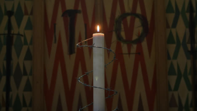 a candle wrapped in barbed wire gently burns - modern art stock videos & royalty-free footage