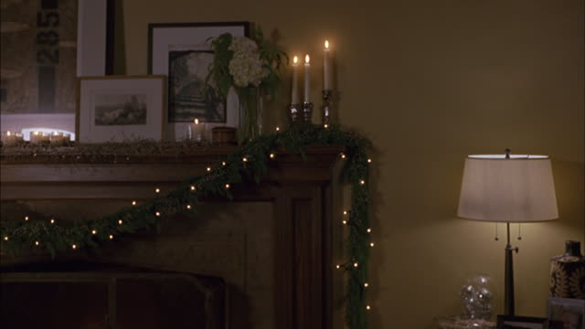 Candles and a lamp illuminate Christmas decorations hanging on a mantel.