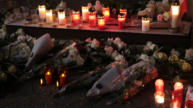candles and flowers lie among the names of victims at a memorial shortly after its inauguration at the site of the 2016 christmas market terror... - identität stock-videos und b-roll-filmmaterial