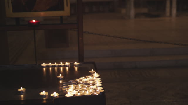 candles and religious painting, sea of galilee, tabgha, church of the multiplication - votive candle stock videos and b-roll footage