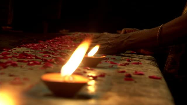 candles burn in a line on an altar. - kerzenschein stock-videos und b-roll-filmmaterial