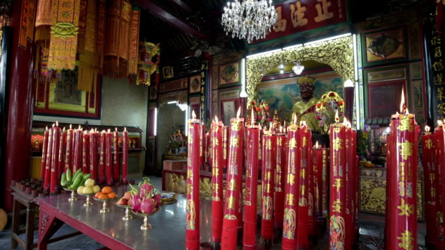vídeos de stock e filmes b-roll de candles burn in front of an altar in a chinese temple - figura masculina