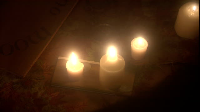 candles burn on a seance table beside a spirit board. - mystery stock videos & royalty-free footage