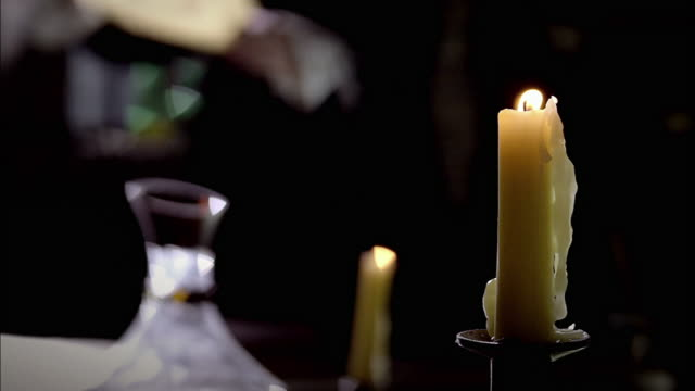 candles burn on a table as nostradamus reads a parchment by the light of a window. - parchment stock videos & royalty-free footage