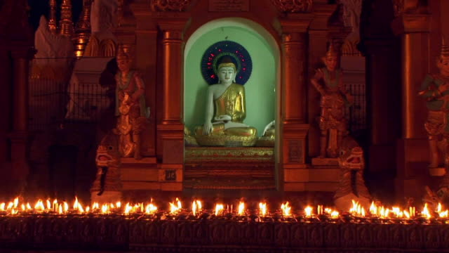 vídeos y material grabado en eventos de stock de candles burning in front of buddha - candlelight