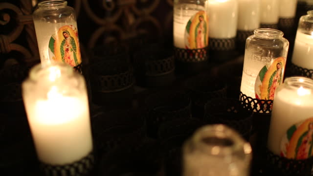 candles burning inside of a church. - female likeness stock videos & royalty-free footage