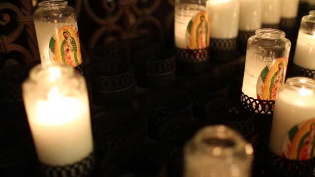 vídeos de stock, filmes e b-roll de candles burning inside of a church. - figura feminina