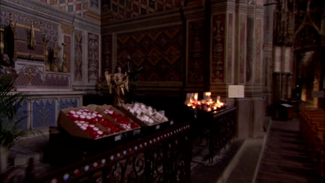 Candles flicker before a small chapel containing a statue of Saint Cecilia's body in Albi Cathedral Available in HD.