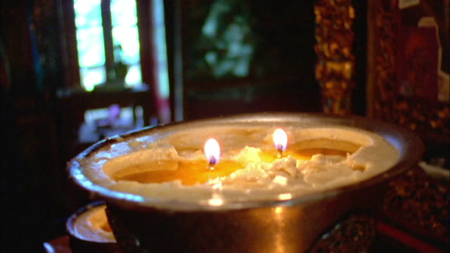candles flicker in bowls beneath buddhist shrine available in hd. - shrine stock videos & royalty-free footage