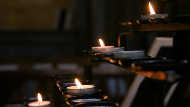 cu candles gently burning in cathedral - kerzenschein stock-videos und b-roll-filmmaterial