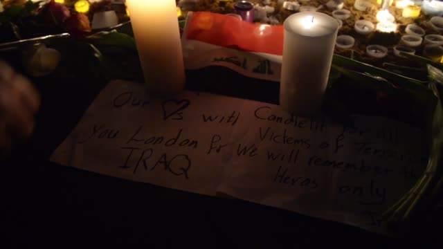 candles illuminate the iraqi national flag and the solidarity message of a person thought to be from iraq as a tribute to the three people killed and... - ウェストミンスター橋点の映像素材/bロール