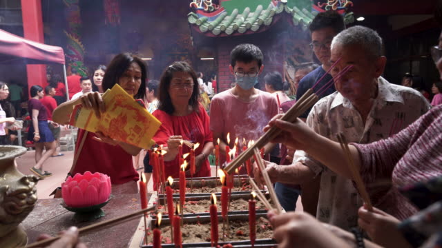 candles lighting the incense sticks at temple - kuala lumpur stock videos & royalty-free footage