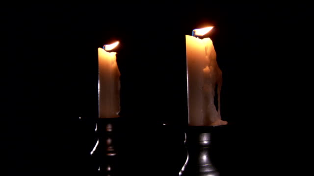 candlesticks support two candles with flickering flames in a dark room. - candlelight stock-videos und b-roll-filmmaterial