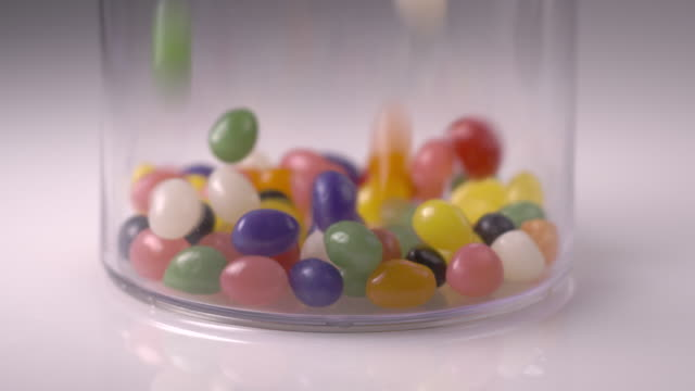 candy jelly beans fall in to a cylinder in slow motion. - ジェリービーンズ点の映像素材/bロール