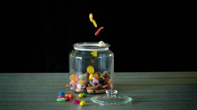 stockvideo's en b-roll-footage met candy pouring into a jar in slow motion - zoet voedsel