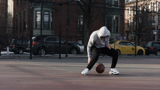a canid caucasian male in his twenties practices basketball at a local brooklyn court - 4k - sweatshirt stock videos & royalty-free footage