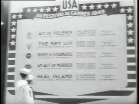 stockvideo's en b-roll-footage met cannes film festival france harbor night ext large hall sailor reading poster of american film titles descriptions large outdoor garden of tables mcu... - 1949