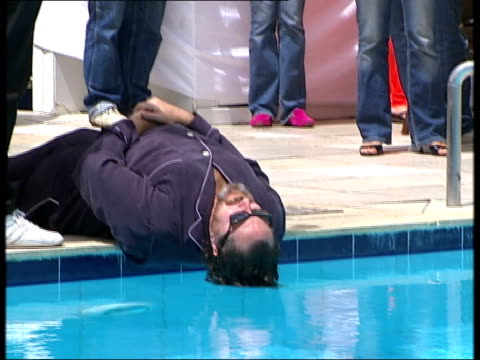 vidéos et rushes de julian schnabel and mathieu almaric interviews france cannes ext julian schnabel lying by swimming pool fully clothed with his hair immersed in the... - festival de film