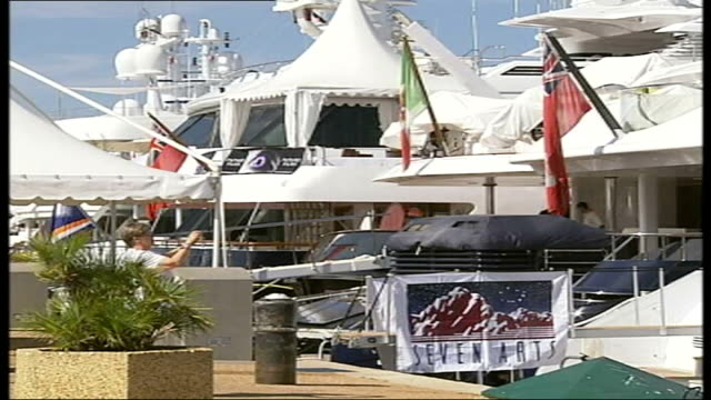 preview france cannes ext large white umbrellas on beach large yachts moored at quayside people on yacht chatting line of flags fluttering in wind... - casino poster stock videos & royalty-free footage