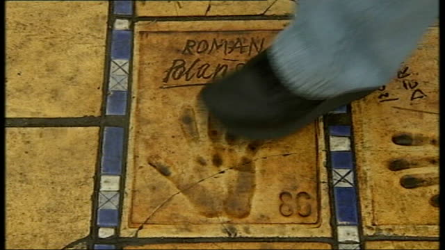 stockvideo's en b-roll-footage met cannes film festival starts close shot of roman polanski's hand print low angle shot of people walking over hand prints in pavement - roman polanski