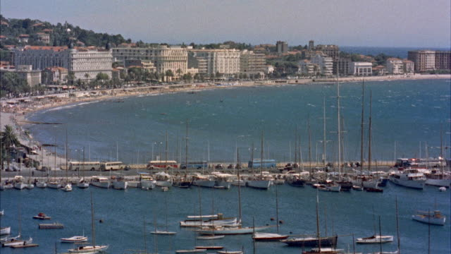 stockvideo's en b-roll-footage met ws cannes harbor with town, yacht harbor in foreground / cannes - 1955