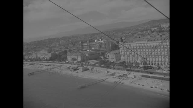 vídeos de stock e filmes b-roll de aerials fly-by of cannes harbor, with parts of camera plane in shots / marseilles: boats at dock, with man walking up gangplank to board boat as... - 1930