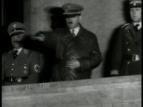 vidéos et rushes de cannon firing night hitler standing on balcony saluting nazi salute almost wave of hand german nazi soldiers troops marching goosestep in street - 1934