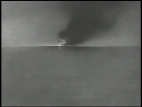 Cannons on deck of battleship firing several times lighting up deck WS Animated ship on horizon on fire smoking VS More firing deck lighting up...