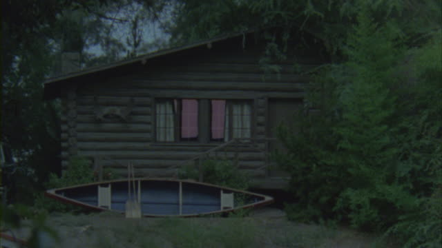 A canoe leans against a cabin in a forest.