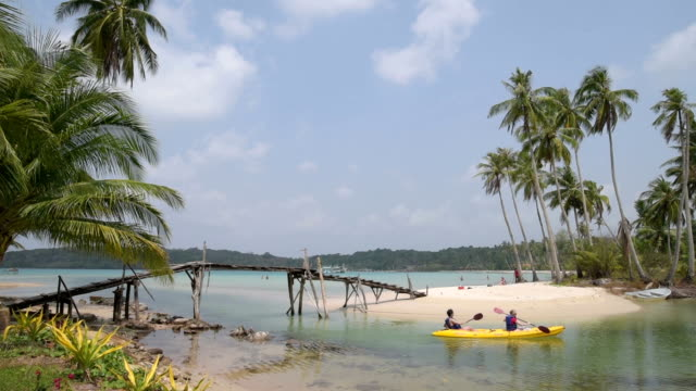 a canoe travels under a wooden footbridge, leading to a beach - trat province stock videos and b-roll footage