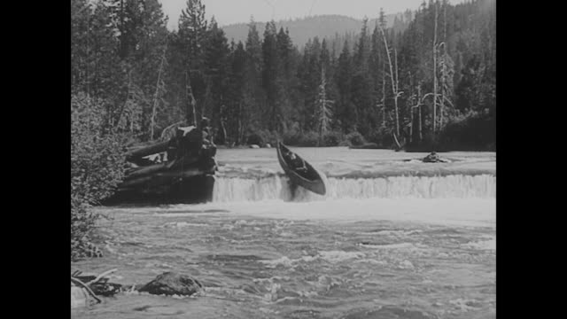vídeos de stock, filmes e b-roll de 1923 a canoeing man (buster keaton) goes over a waterfall - 1923