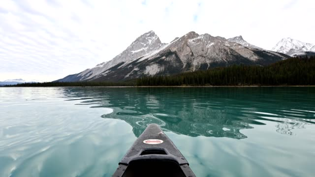 canoeing on maligne lake with canadian rockies in jasper - clear sky stock videos & royalty-free footage