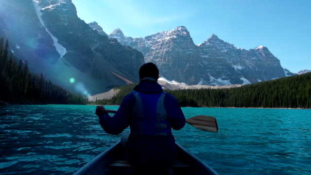 stockvideo's en b-roll-footage met canoeing on mountain lake - canada