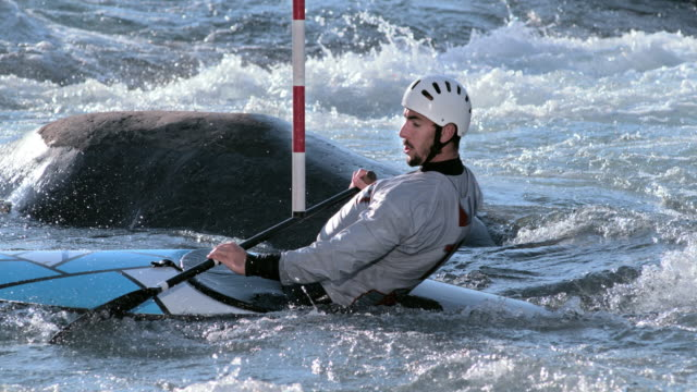 vídeos de stock, filmes e b-roll de slo mo canoeist going through hanging gates on the slalom course - canoagem