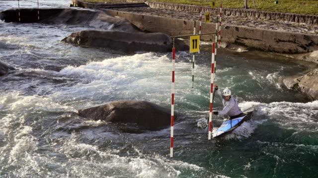 vídeos de stock, filmes e b-roll de aerial canoeist paddling through the gates on a slalom course in a competition - esporte de competição
