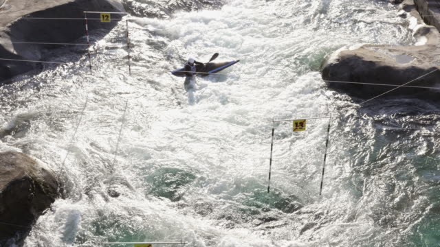 vídeos de stock, filmes e b-roll de aerial canoeist paddling through the gates on a slalom course in sunshine - canoagem